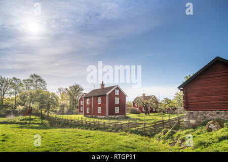 Old farm house and traditional roundpole fence in a rural landscape at the village Stensjo by in Smaland, Sweden, Scandinavia - Stock Photo