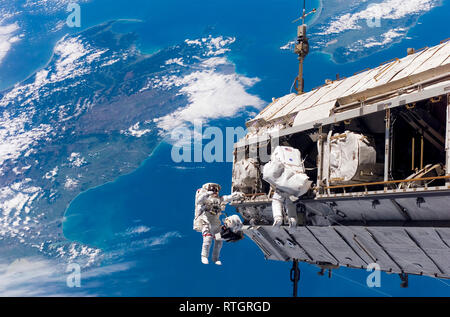 Astronauts on a space walk and the International Space Station with a view of Earth