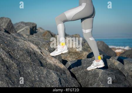close up of a woman runners legs in leggings running across rocks - Stock Photo
