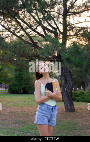 Happy female student is holding a book and dreaming about something. Pretty woman is smiling and walking in the park. - Stock Photo