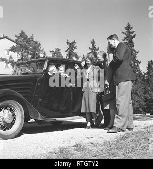 Lifestyle in the 1950s. A young couple in their camera saying goodbye to a group of people they have visited. Photo Kristoffersson Ref BF77-2. Sweden 1952