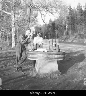Lifestyle in the 1950s. A young couple has stopped to have a coffee and a sandwich by the roadside. An old millstone makes a good table for the picnic. Photo Kristoffersson Ref BF76-4. Sweden 1952 - Stock Photo