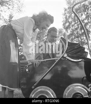 Parents in the 1950s. A proud mother and father are looking down on their child in the baby carriage. The baby carriage has a typical 1940s design with a wooden body painted in black. Notice the chrome details on the side, covering the wheels. Photo Kristoffersson ref AX39-7 Sweden 1950 - Stock Photo