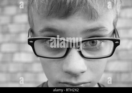 Black and white macro shot of upset preteen boy wearing glasses - Stock Photo