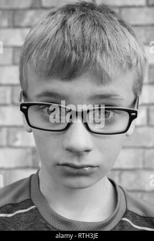 Black and white portrait of upset preteen boy wearing glasses - Stock Photo