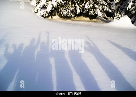 Shadows of hikers fooling around on a snow background. Simple, abstract, minimalist winter scene on a bright February day. - Stock Photo