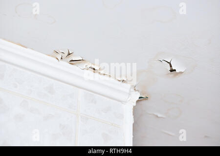 Swelling leaking of whitewash and plaster on ceiling of dwelling due to penetration of water from the top floor or roof. - Stock Photo