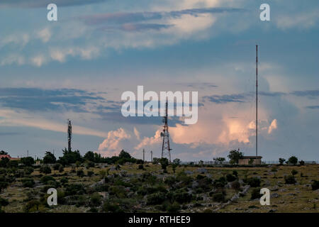Communication towers and antennas against cloudy sunset sky with space for text, photo made near Matera, the Sassi di Matera, Basilicata, Southern Ita - Stock Photo