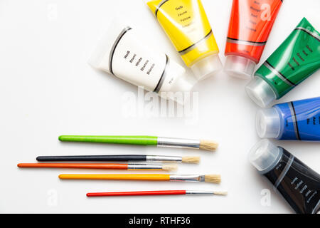 Brushes with acrylic color tubes. Colorful acrylic paints over white background - Stock Photo