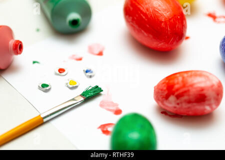 Easter eggs colored manual with paintbrush over white table - Stock Photo