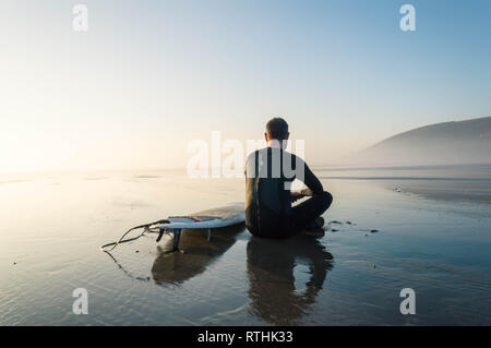 A surfer sitting by a surfboard on a misty afternoon looking out tosea. Saunton, Devon, UK. - Stock Photo