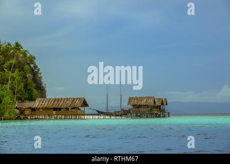 Indonesia. Raja Ampat archipelago. Cloudy evening. Coast of the island with a pier for boats and houses on stilts. Two-masted schooner in the backgrou - Stock Photo