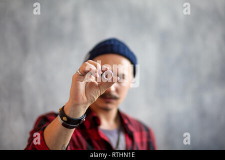 young man evaluating the ring. close up photo.focus on the luxury expensive ring, crime concept - Stock Photo