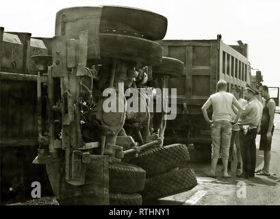 Drivers and policeman near fallen truck - Stock Photo