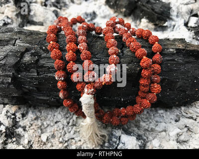 Rosary prayer beads on the ash cinder background. Rudraksha. Mala. Mantra. 108 beads.