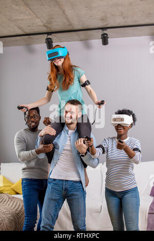 Multiracial group of people having fun and giving piggyback ride to joyful woman in vr glasses - Stock Photo