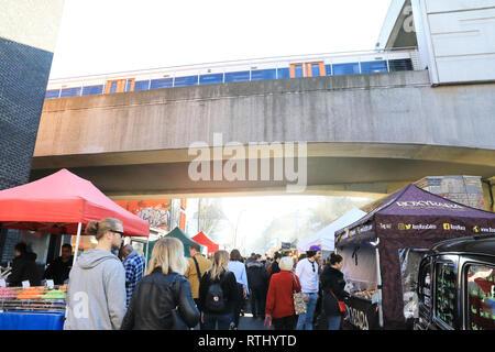 Overground train passing over vibrant Sunday Brick Lane Market in Bethnal Green in east London, UK - Stock Photo