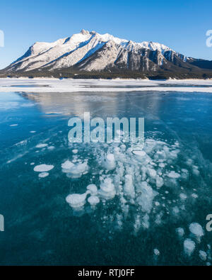 Cracks and methane bubbles trapped in ice covering Abraham Lake with Mount Michener in the background, Alberta, Canadian Rockies, Canada - Stock Photo