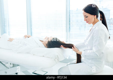 Cosmetology image of beautician doing head massage or prepare female patient to hardware cosmetology procedures. Beauty concept. Cosmetology concept.  - Stock Photo