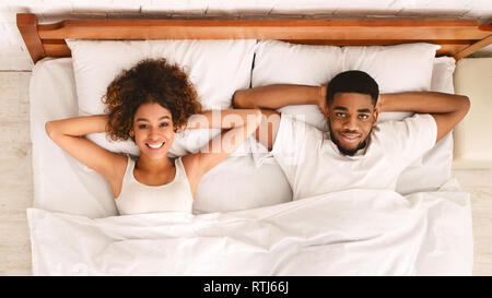 African-american lovers relaxing in bed in hotel room - Stock Photo