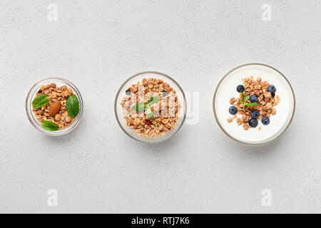 Granola, yogurt, blueberries in bowls on grey background, top view. Gluten free meal concept - Stock Photo