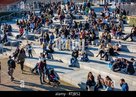 Many people sitting in the sun on steps next to the Regents Canal in front of Coal Drops Yard, Kings Cross, London, England - Stock Photo