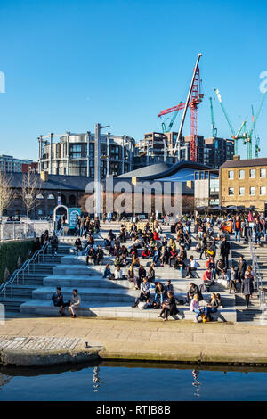 Many people sitting in the sun on steps next to the Regents Canal in front of Coal Drops Yard and Gasholders Contemporary Apartments, London - Stock Photo