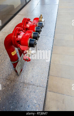 2 Contemporary Red Fire Hydrants and Dry Riser outside the Universal Music UK headquarters at Four Pancras Square, Kings Cross, London - Stock Photo