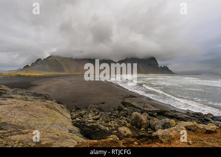 Magical landscape of Vestrahorn Mountains and Black sand dunes in Iceland at sunrise.  Panoramic view of the Stokksnes headland in a Colorful seascape - Stock Photo