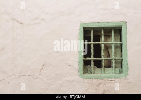 White facade of a house with a small light green frame and grating of a window without glass, partly covered from inside with a pieces of wood. - Stock Photo