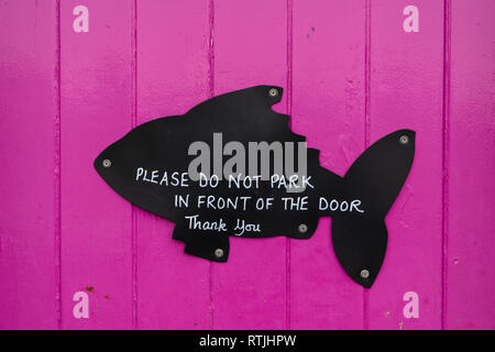 Close up of purple wooden door with black cut out wood fish shape with wording 'please do not park in front of the door, thank you'. - Stock Photo