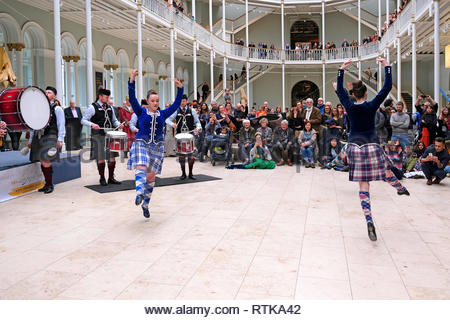 Edinburgh, United Kingdom. 2nd March 2019. Scottish Highland dancers performing with the Stockbridge Pipe Band at the National Museum of Scotland Grand Gallery, part of the Edinburgh Iranian festival, celebrating Iranian culture and integrating communities.    Credit: Craig Brown/Alamy Live News - Stock Photo