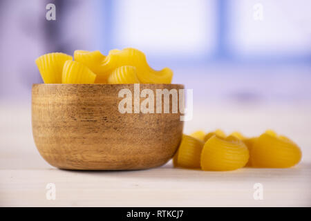 Lot of whole yellow raw pasta pipe rigate variety with wooden bowl with blue window - Stock Photo