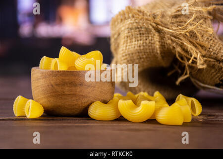 Lot of whole yellow raw pasta pipe rigate variety with wooden bowl in a restaurant - Stock Photo