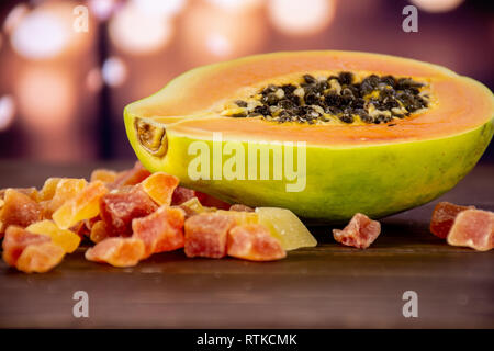 One half lot of slices of dry papaya with lights in dark - Stock Photo