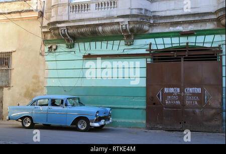 Street scene in Old Havana, Cuba, showing a classic blue car parked in front of a building with a sliding metal door covering an arched entrance. - Stock Photo