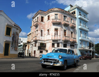 A classic car drives along a road in Old Havana, Cuba lined with colorful, historic buildings. Vintage American cars are a common site in the capital. - Stock Photo