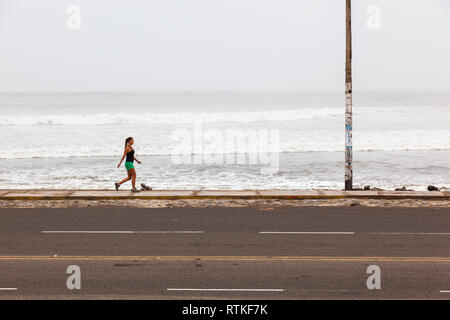 Huanchaco, Peru, July 2018: Young woman walking on the beach of Huanchaco on a cloudy day of Peruvian winter. - Stock Photo