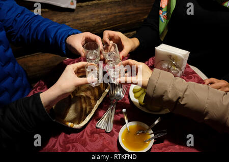 People toasting homemade Samogon distilled alcoholic beverage in Belarus - Stock Photo