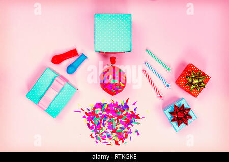 Concept: birthday party. Gift boxes, red and gold bow, colorful candy, balloons on a pink pastel minimalist background. Flat lay - Stock Photo