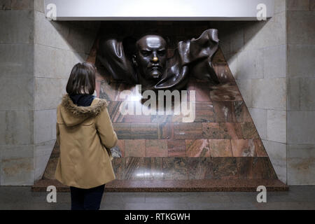 A young Belarusian woman lookinf at the statue of Vladimir Lenin placed inside  Plosca Lienina (Lenin Square) Metro station in Independence Square in the city of Minsk, capital of Belarus - Stock Photo