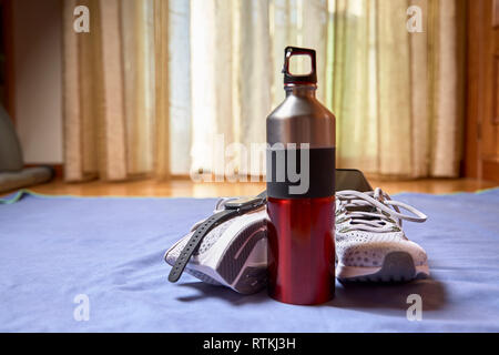 running shoes with technological accessories and next to a pot of water on a blue towel in a room - Stock Photo