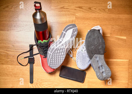 running shoes next to a water bottle and technological accessories on the wooden floor of a gym - Stock Photo