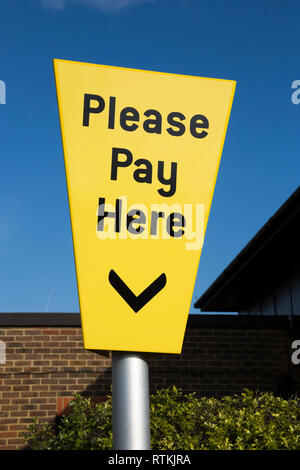 Please Pay Here car parking pay & display sign above a ticket machine at pay point in the car park at NHS Gosport War Memorial Hospital. Hampshire UK - Stock Photo
