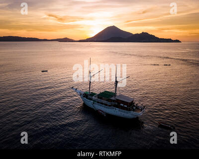 liveaboard dive boat, at sunset, Banda Api, an active volcanic island, in distance, Banda Islands, Maluku Islands, Indonesia, Banda Sea, Pacific Ocean - Stock Photo