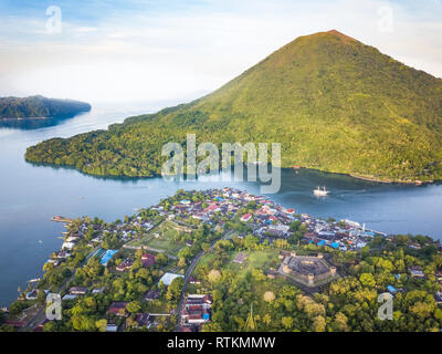 Fort Belgica, a 17th-century fort built by the Dutch on Banda Neira, Banda Api, an active volcanic island, in background, Banda Islands, Maluku Island - Stock Photo