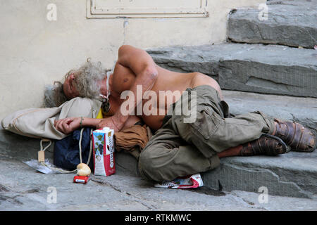 Homeless man sleeping rough on the streets of Florence, Tuscany, Italy, Europe. - Stock Photo