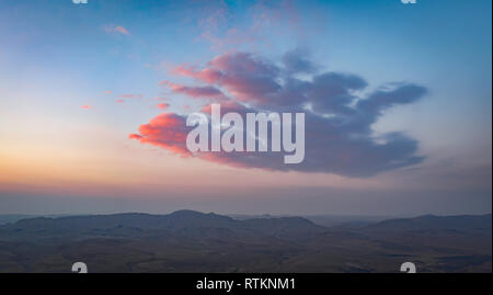 The sunrise over the Negev desert in southern Israel paints the clouds red - Stock Photo