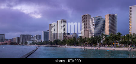 Famous Waikiki Beach on the Hawaiian island of Oahu. View is towards the major hotels in the evening.  People are still visible enjoying the beach - Stock Photo