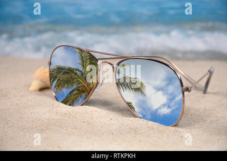 08d2ba3879 ... tropical palm tree reflection in sunglasses with seashell in beach sand  - Stock Photo